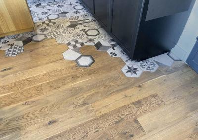 Photo du parquet du salon qui s'incruste avec les carreaux hexagonaux du carrelage de la cuisine